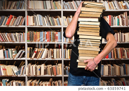 A young man holds a stack of books 63859741