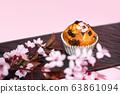 Chocolate muffin and cherry blossoms sakura, homemade bakery on dark and pink background. 63861094