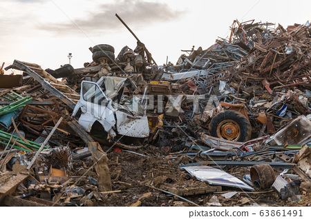 The remains of a truck cabin, wheels and mountains of metal pieces in a junkyard 63861491