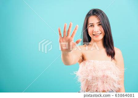 Smiling face Asian beautiful woman showing hand 63864081