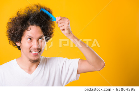 Asian man combing curly hair on yellow background 63864598