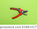 Garden pruning shears on a green background 63881417
