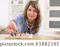 Beautiful young woman playing chess at home 63882165