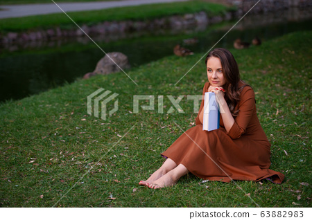 Woman is resting in park and reading book 63882983