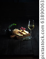 Glass of cold white wine with cheese snack on a wooden. catering menu 63890063