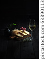 Glass of cold white wine with cheese snack on a wooden. catering menu 63890113