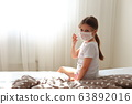 Girl in a respiratory mask sits in quarantine at home. 63892016