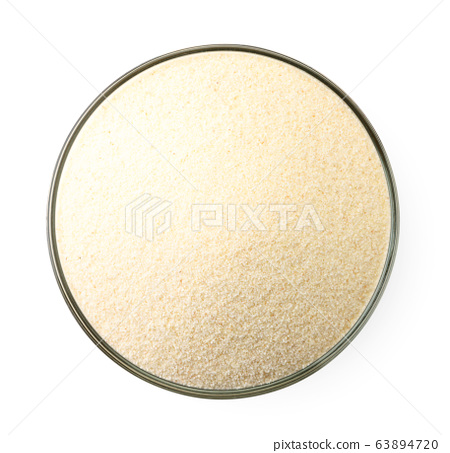 Semolina in a plate on a white. The view from top 63894720