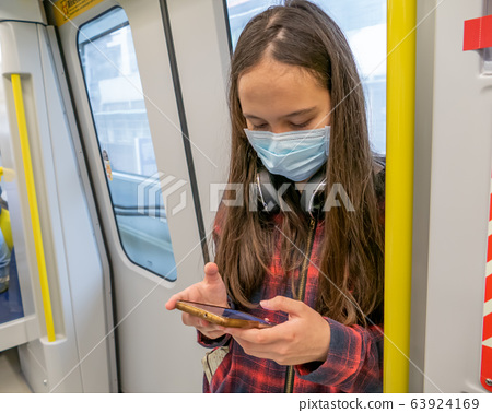 Young tween girl wearing surgical mask on subway 63924169