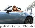 A woman riding a car 63925563