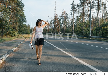 Mature woman walking along the road, looking at the road 63925571