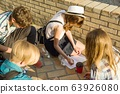 Communication and recreation group of 4 children teenagers. Friends play board game, throwing dice. Background city street 63926080