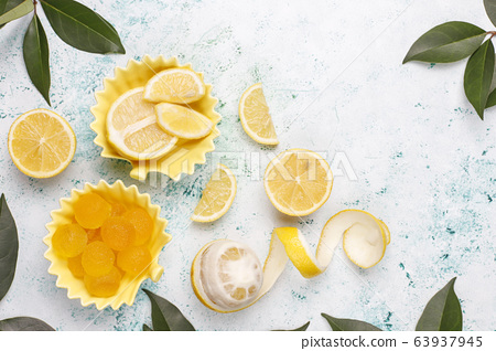 Lemon jelly candies with fresh lemons on light background,top view 63937945