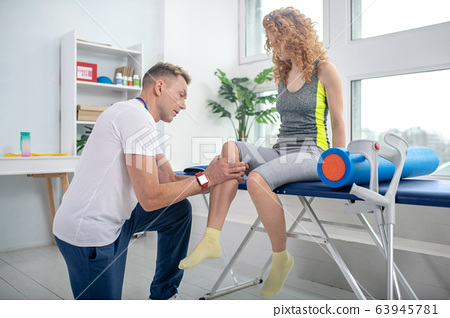 Male physiotherapist kneeling on one knee, examining painful knee of female patient 63945781