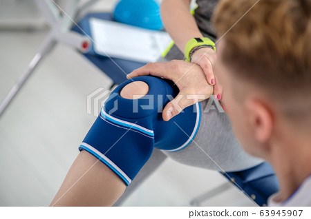 Male physiotherapist hands examining knee bandage of female patient 63945907