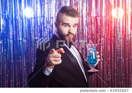 Club party and holidays concept - Portrait of elegant handsome man in a expensive suit holds blue cocktail on shiny background. 63950887