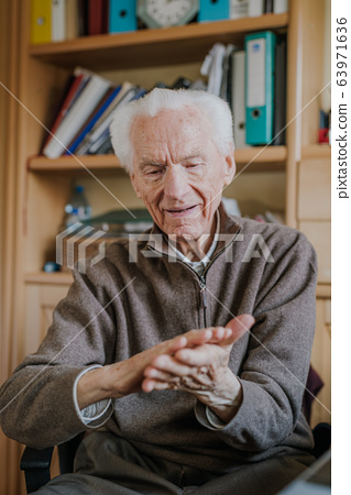 Old man disinfects hands with antibacterial liquid 63971636