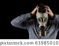 a man in a gas mask is worried about the current situation 63985010