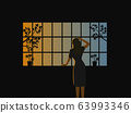 The woman stood looking out the window with morning sunlight in the background 63993346