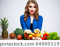 Woman at a table holding a kiwi and pills on a background of fruit and vegetables 64000319