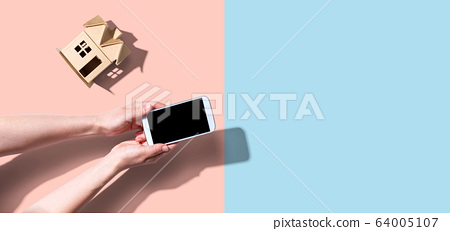 Person using a smartphone with a miniature house 64005107