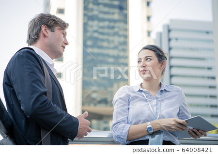 Discussion of businessman and businesswoman at 64008421