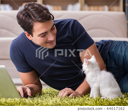 Young handsome man playing with white kitten 64017162