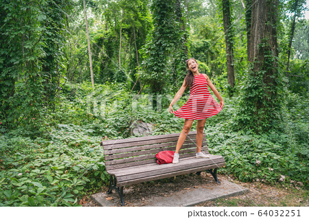 Happy summer carefree Asian girl enjoying freedom in nature after self isolation quarantine from COVID-19 outbreak. Enjoying free walk dancing with red dress in the park 64032251