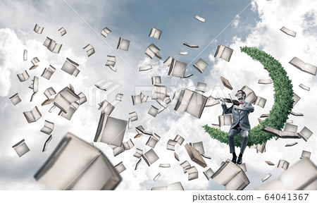Handsome violinist play his melody and books flying around 64041367