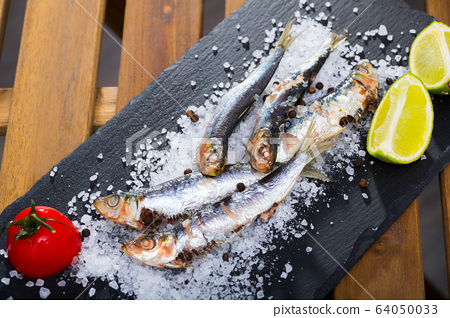 Tasty dish of baked sprat baked in the oven on a pillow of sea salt 64050033