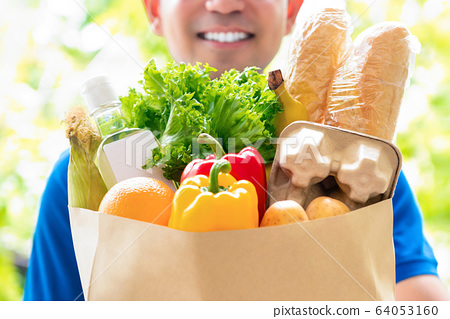 Smiling delivery man holding a grocery bag 64053160