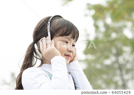 一個女孩在戶外聽音樂的肖像 64055429