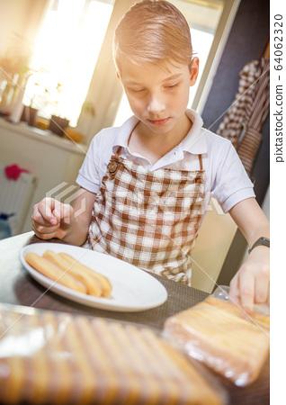 Fun boy stacking sweet cookies preparing tiramisu 64062320