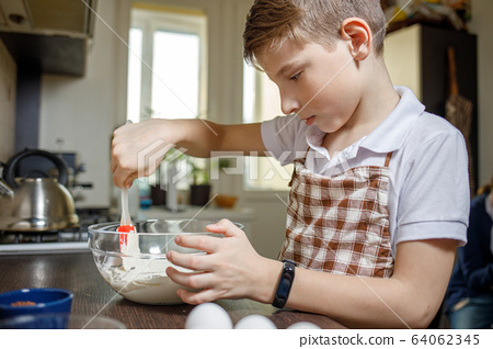 Small cute boy cooking dessert on the kitchen 64062345