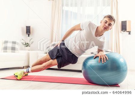 Handsome young adult doing bodyweight workout in 64064996