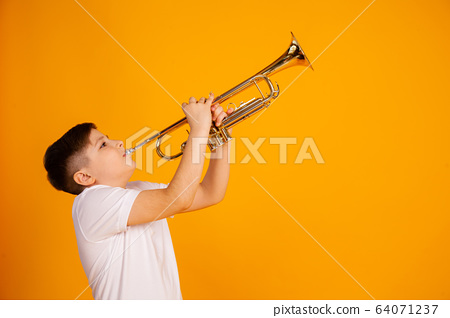 A boy plays the trumpet. Beautiful teenager boy plays trumpet musical instrument 64071237