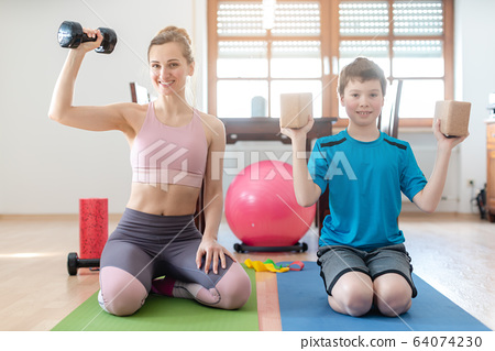 Mother and son doing weight training at home during lockdown curfew 64074230