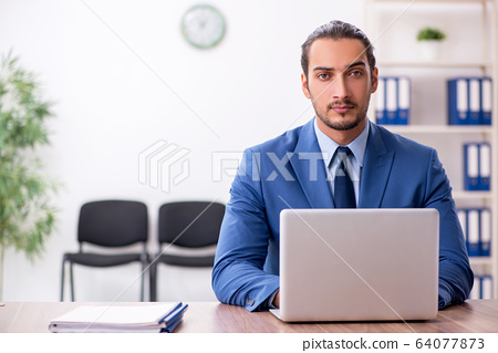 Young male businessman working in the office 64077873