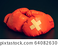 Red boxing gloves in the dark background. Adhesive plaster across each other on boxing gloves. The idea of getting hurt or combat losing business rivals. The idea of fighting giving up boxing. 64082630