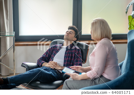 Blonde psychologist having therapy session with a patient 64085171