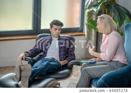 Young man having a therapy session and feeling distressed 64085178