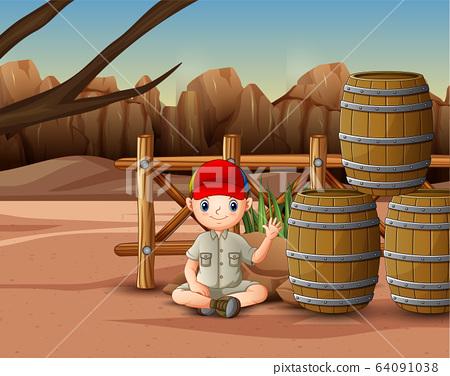 Safari boy sitting near the barrels 64091038