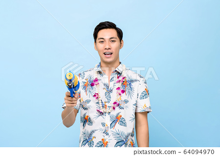 Smiling handsome Asian man playing with water gun 64094970