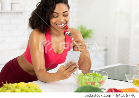 Black girl using smartphone and eating vegetable salad 64106746