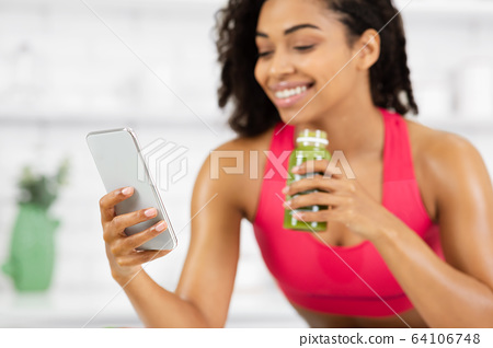 Smiling Girl Drinking Smoothie And Checking Social Media 64106748