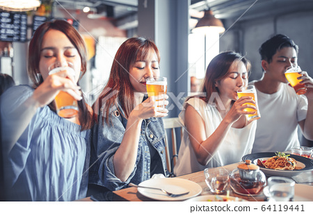 happy young group dining and drinking beer at 64119441