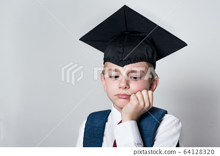 Sad boy in a student hat propped his head with his 64128320