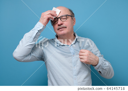 Senior employee sweating in a warm office wiping a forehead 64145718