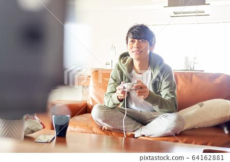 男人在房間裡玩遊戲 64162881