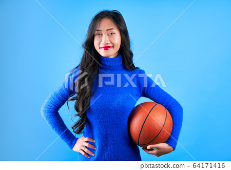 Young pretty woman with basketball in hand isolated on blue background 64171416